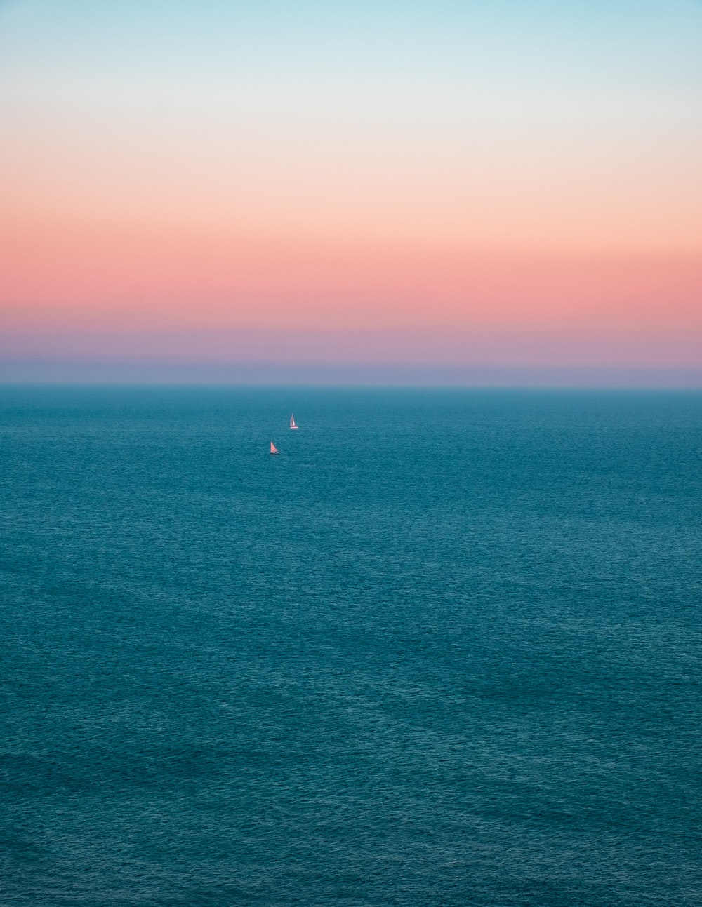 person in the middle of ocean during sunset