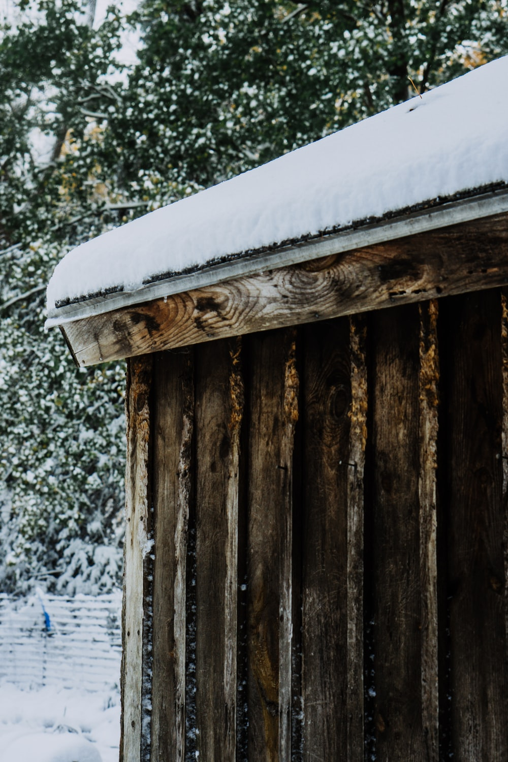 brown wooden fence covered with snow