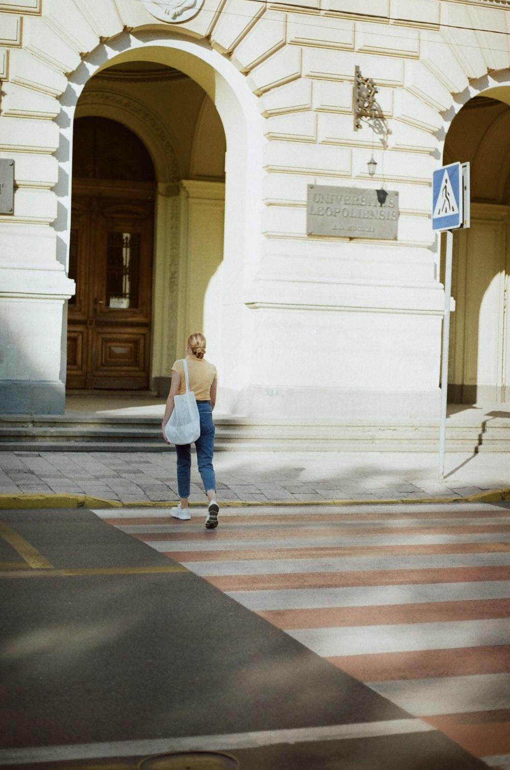 woman in blue denim jacket walking on pedestrian lane during daytime