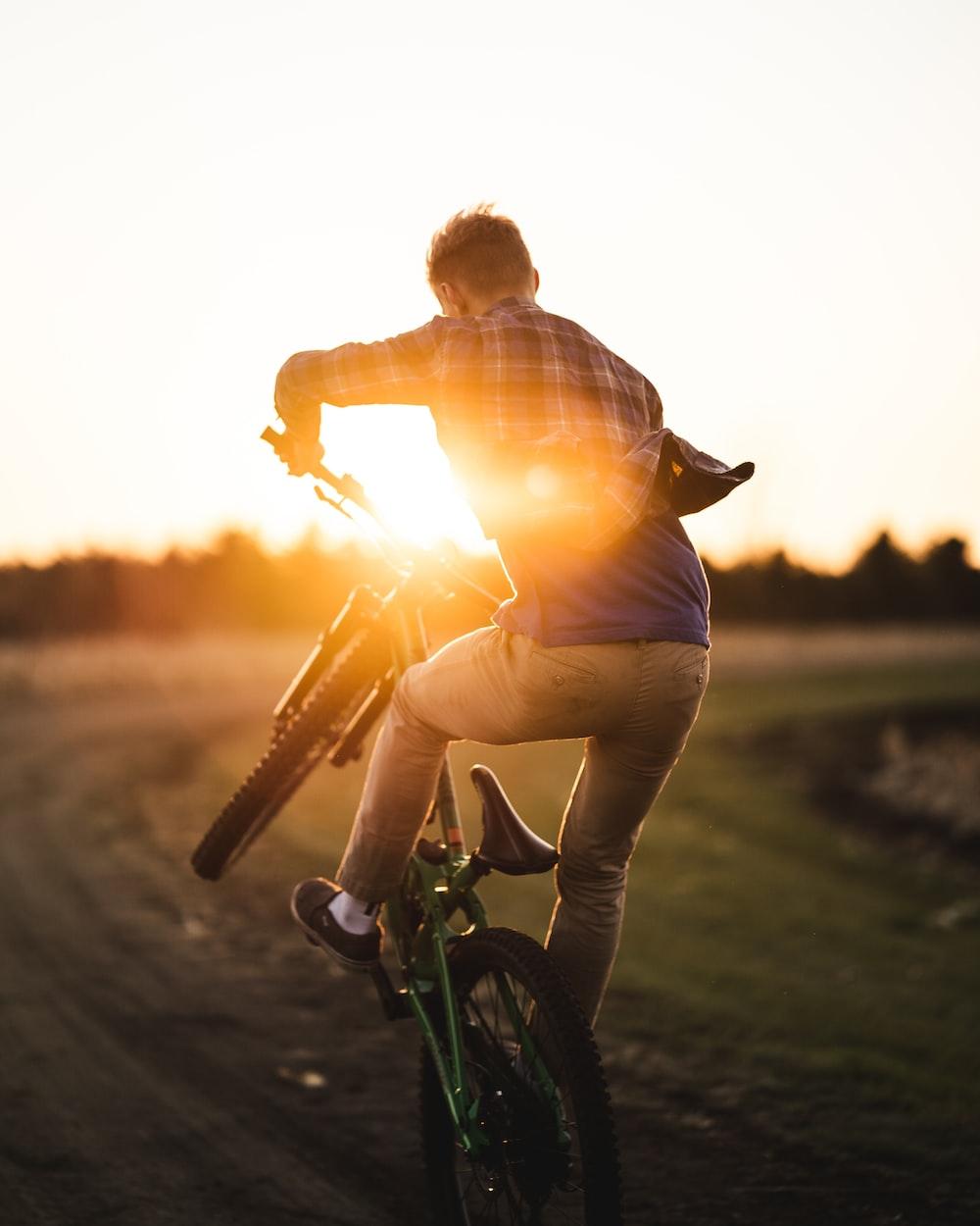 man in brown shirt riding bicycle during sunset