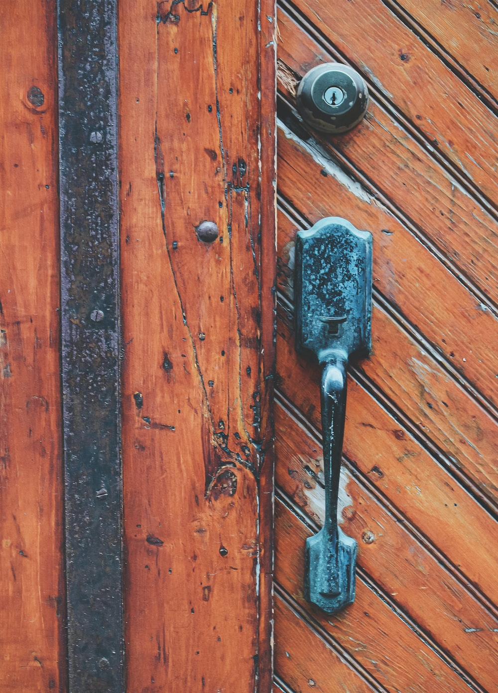 black and silver key on brown wooden surface