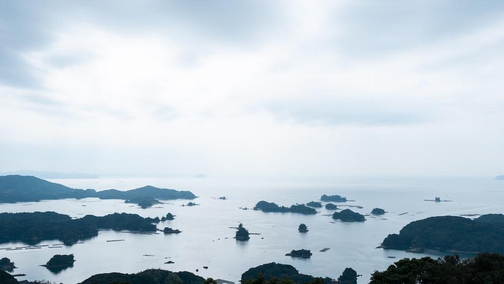 black rocks on body of water under white sky during daytime