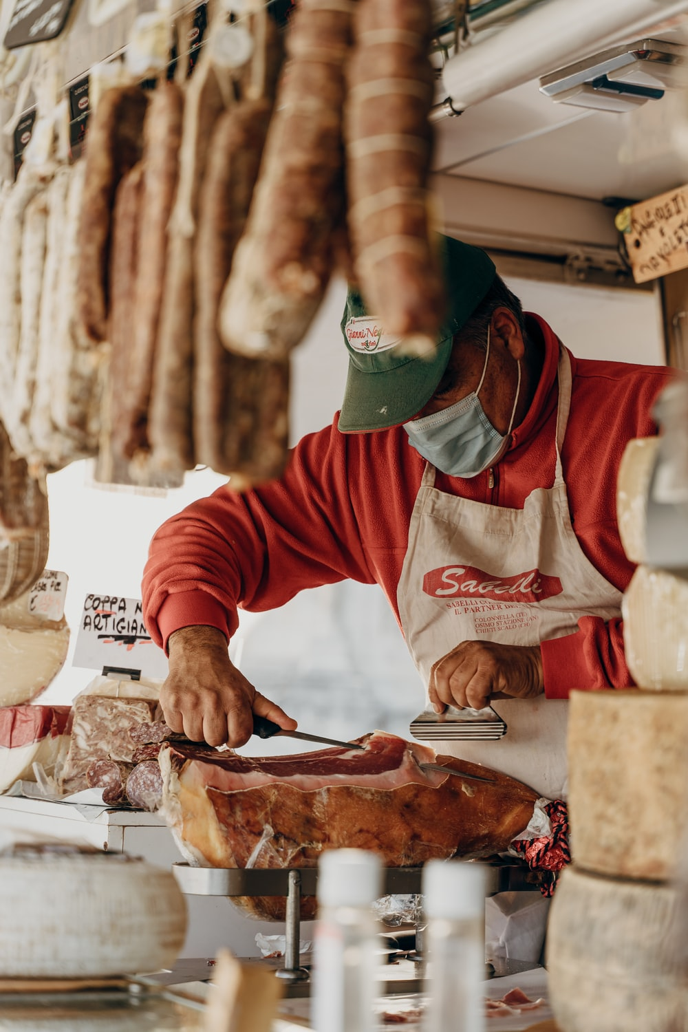 person in red and white long sleeve shirt slicing meat