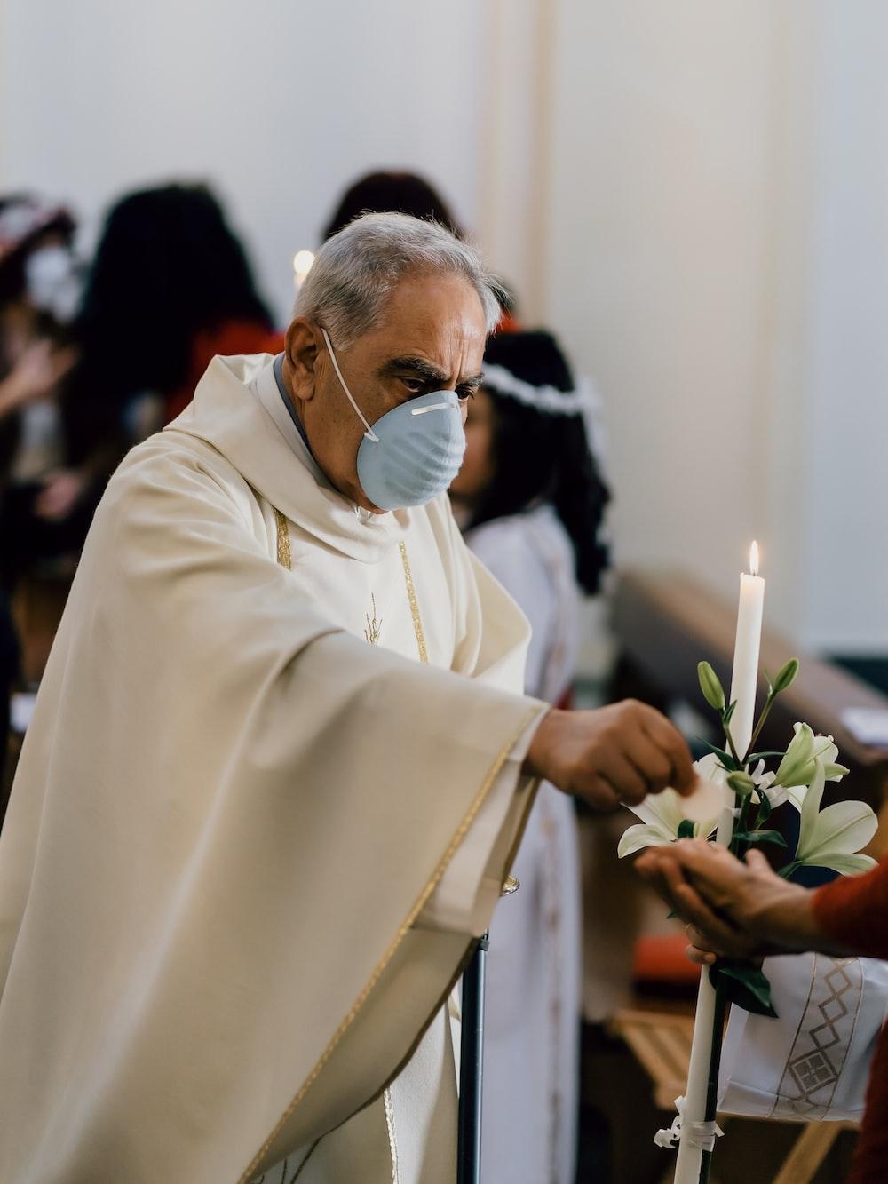 man in white dress shirt holding white flower