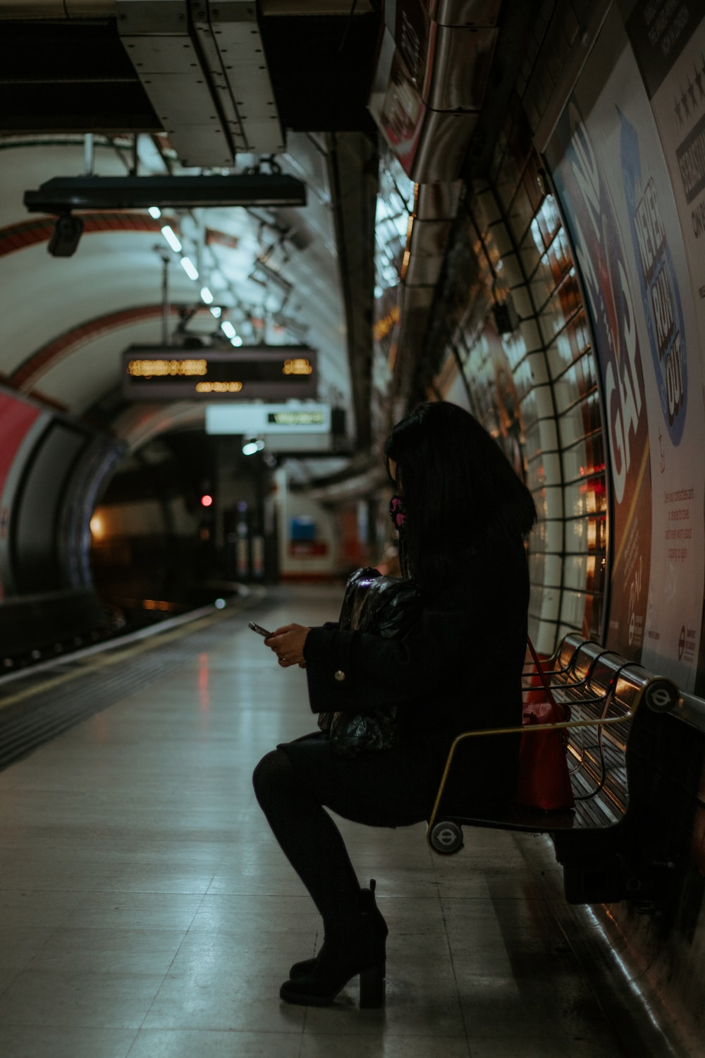woman in black jacket sitting on red metal bench
