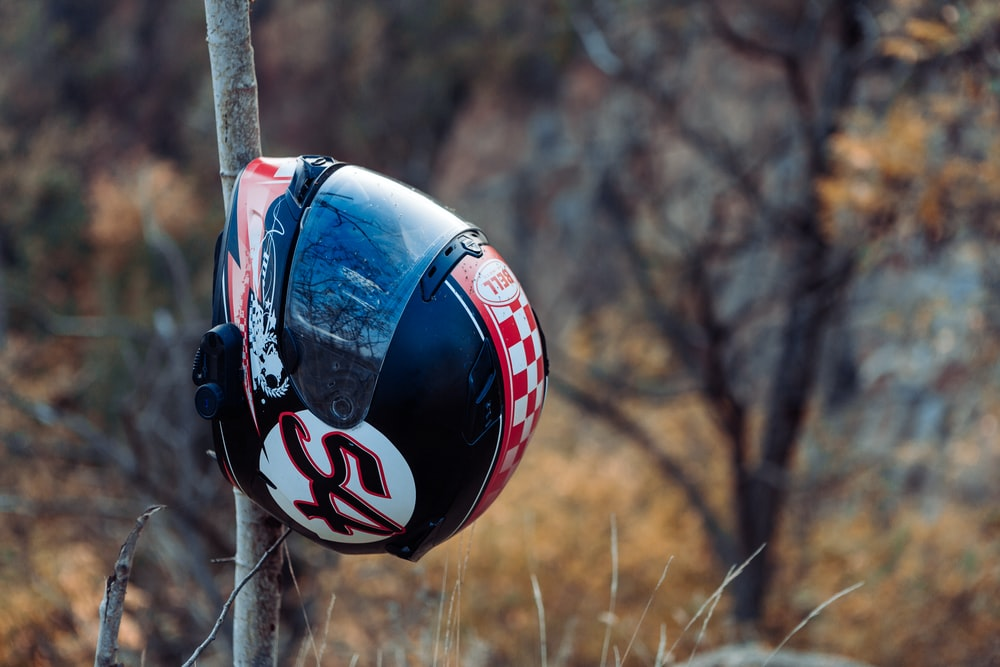 red and black helmet on brown wooden stick