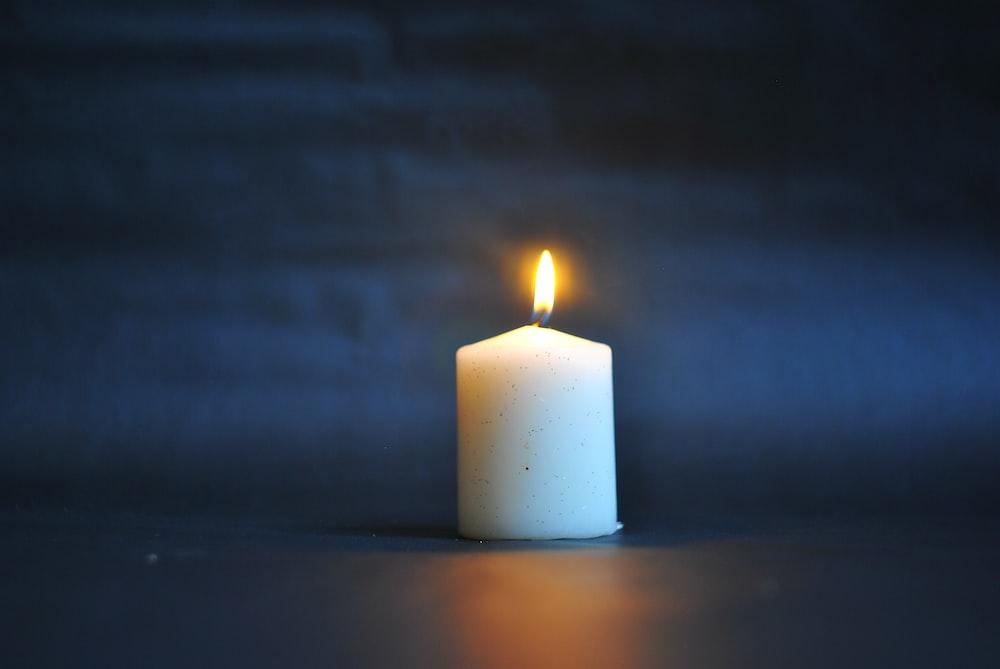 white pillar candle on black surface