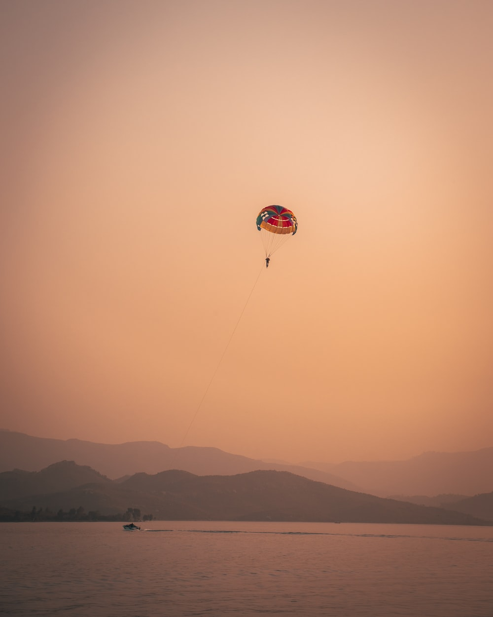 red and white parachute over the mountains during sunset