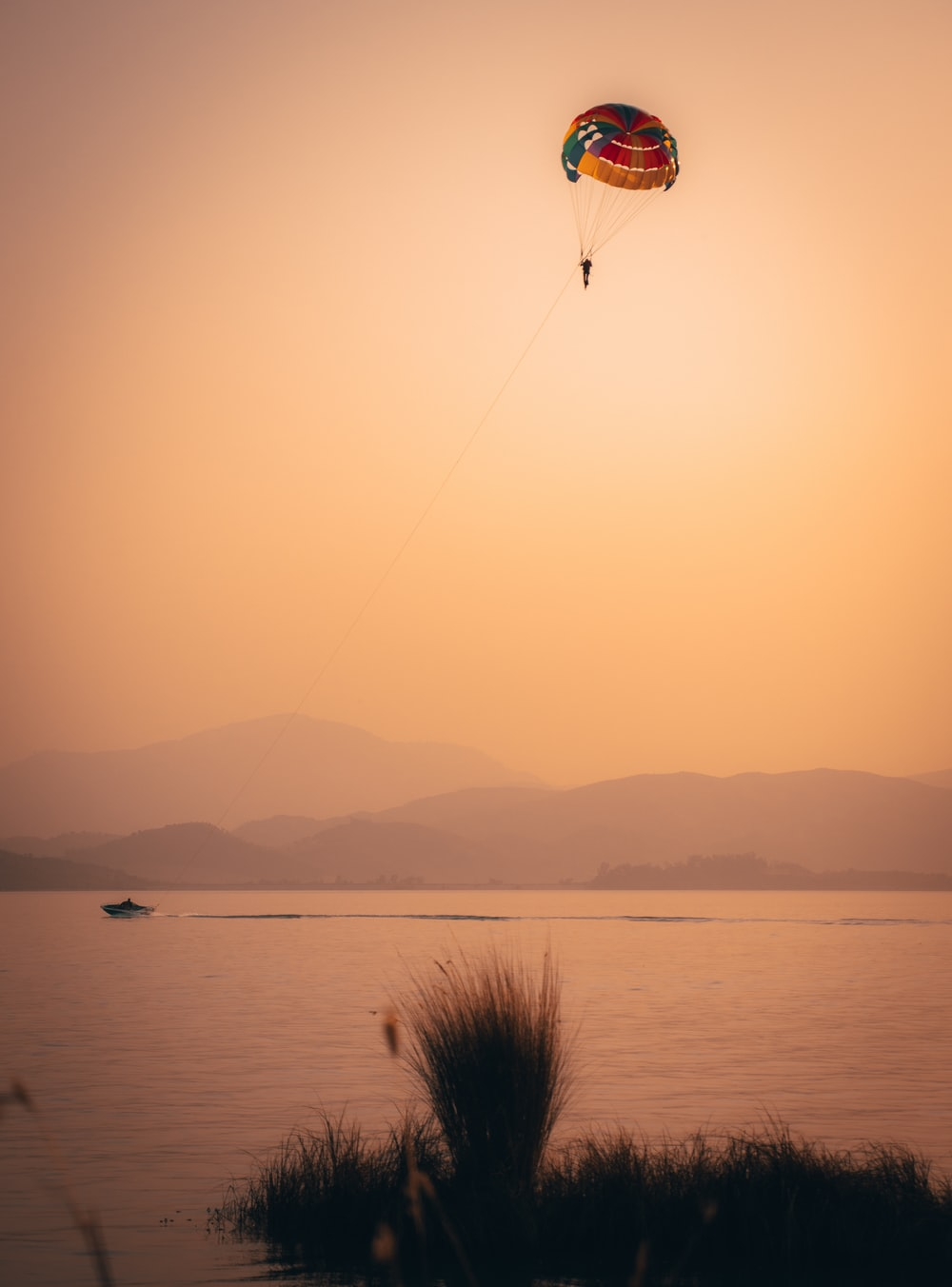 person on parachute over the sea during daytime