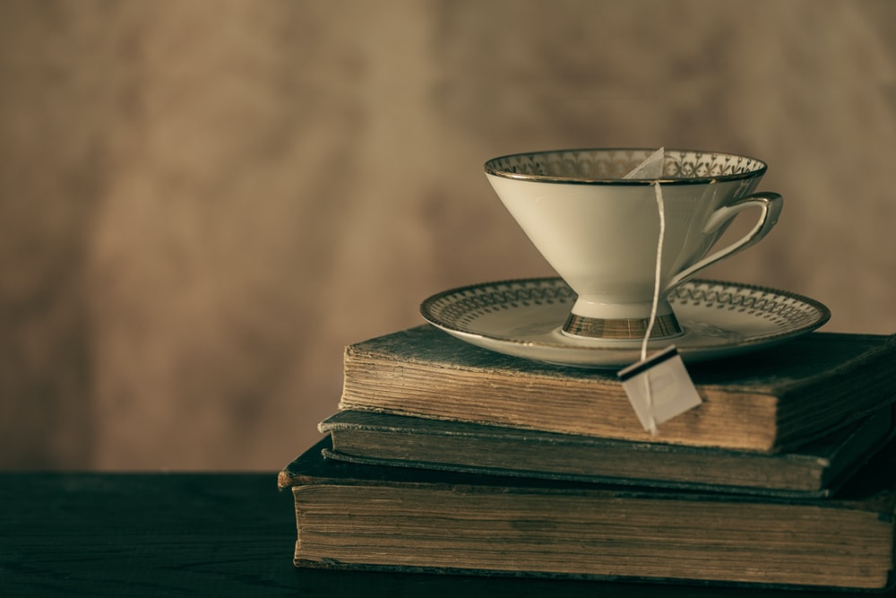 white ceramic teacup on book