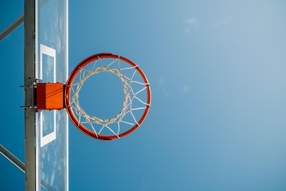 white and orange basketball hoop under blue sky during daytime