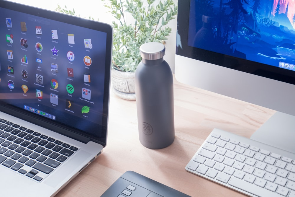 black and silver laptop computer beside white plastic bottle