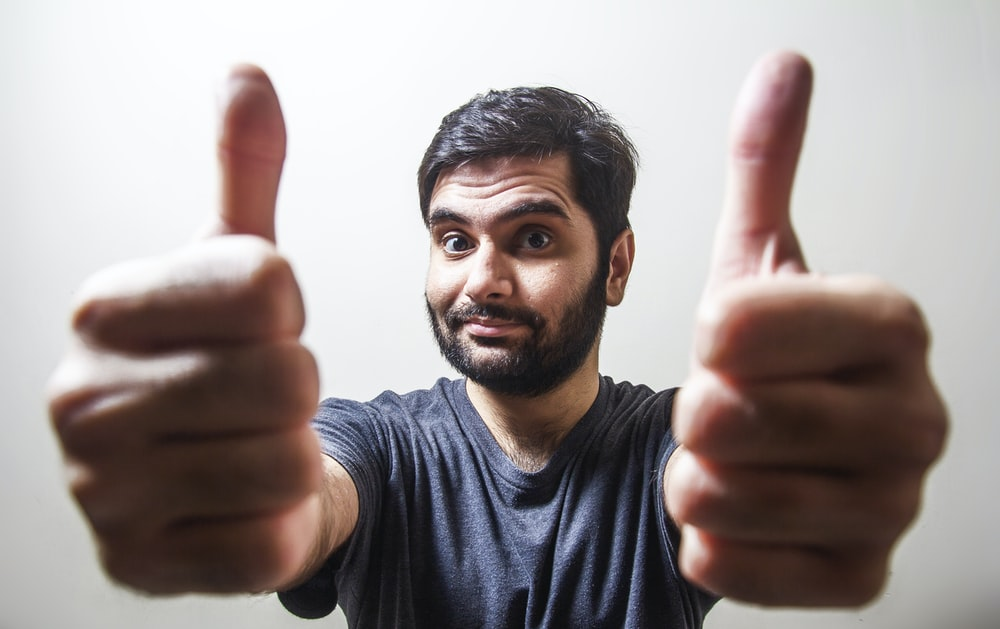 man in gray crew neck shirt making thumbs up