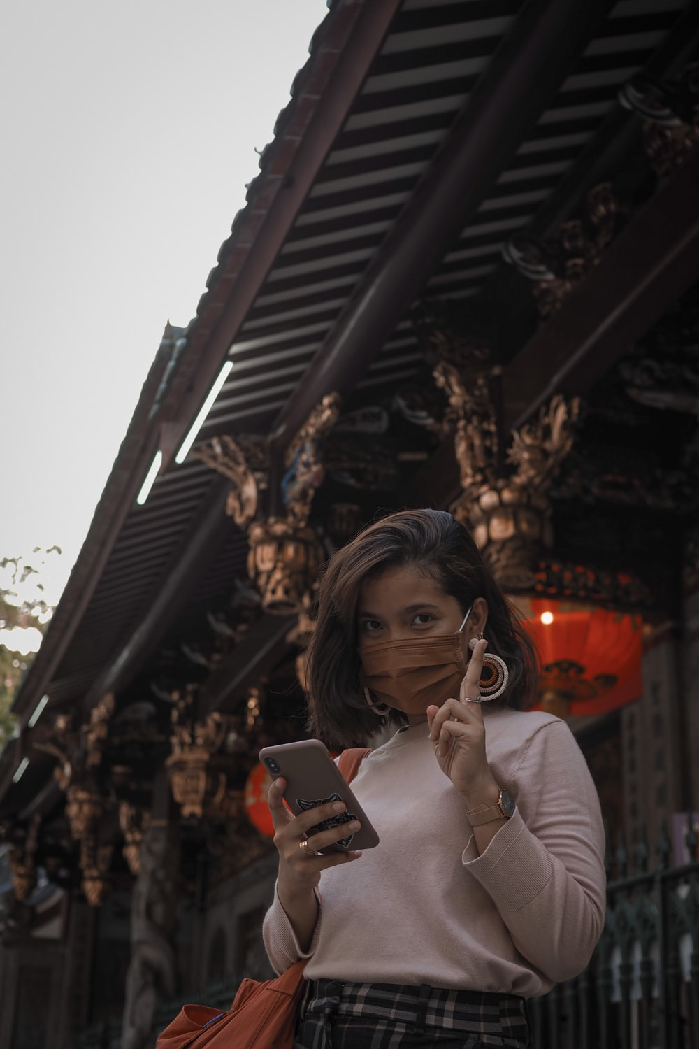 woman in beige long sleeve shirt holding smartphone