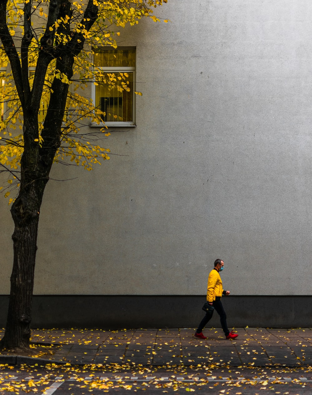 man in yellow jacket and black pants standing beside tree