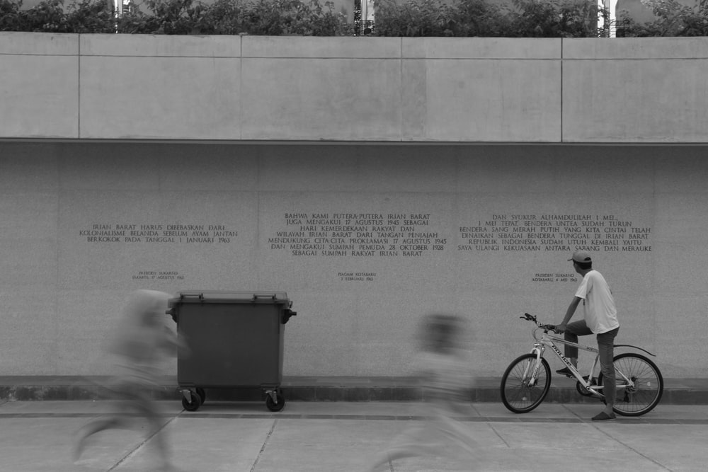 black and white bicycle beside black trash bin