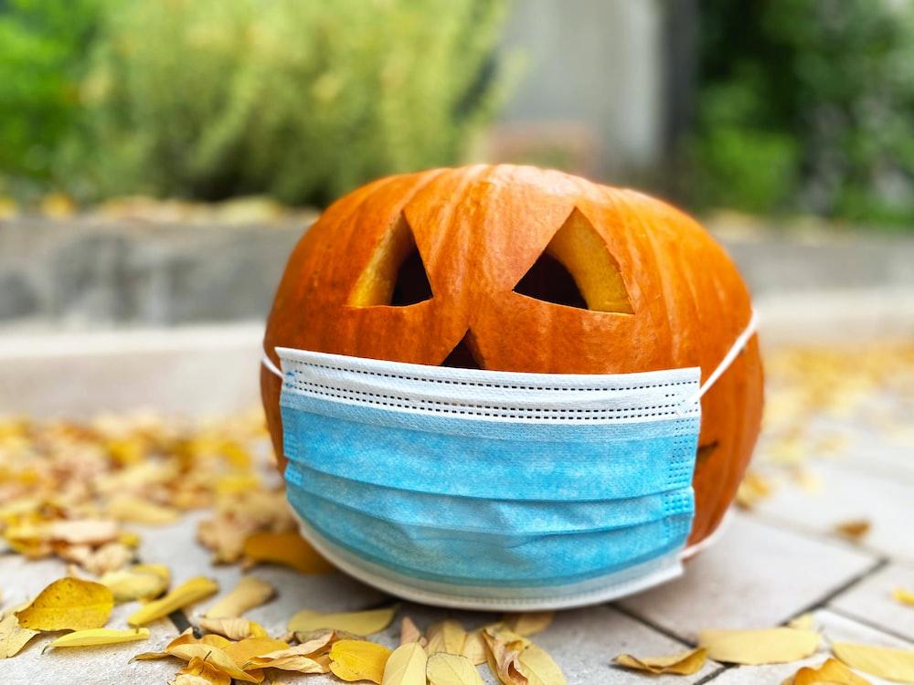 orange jack o lantern on blue and white striped textile