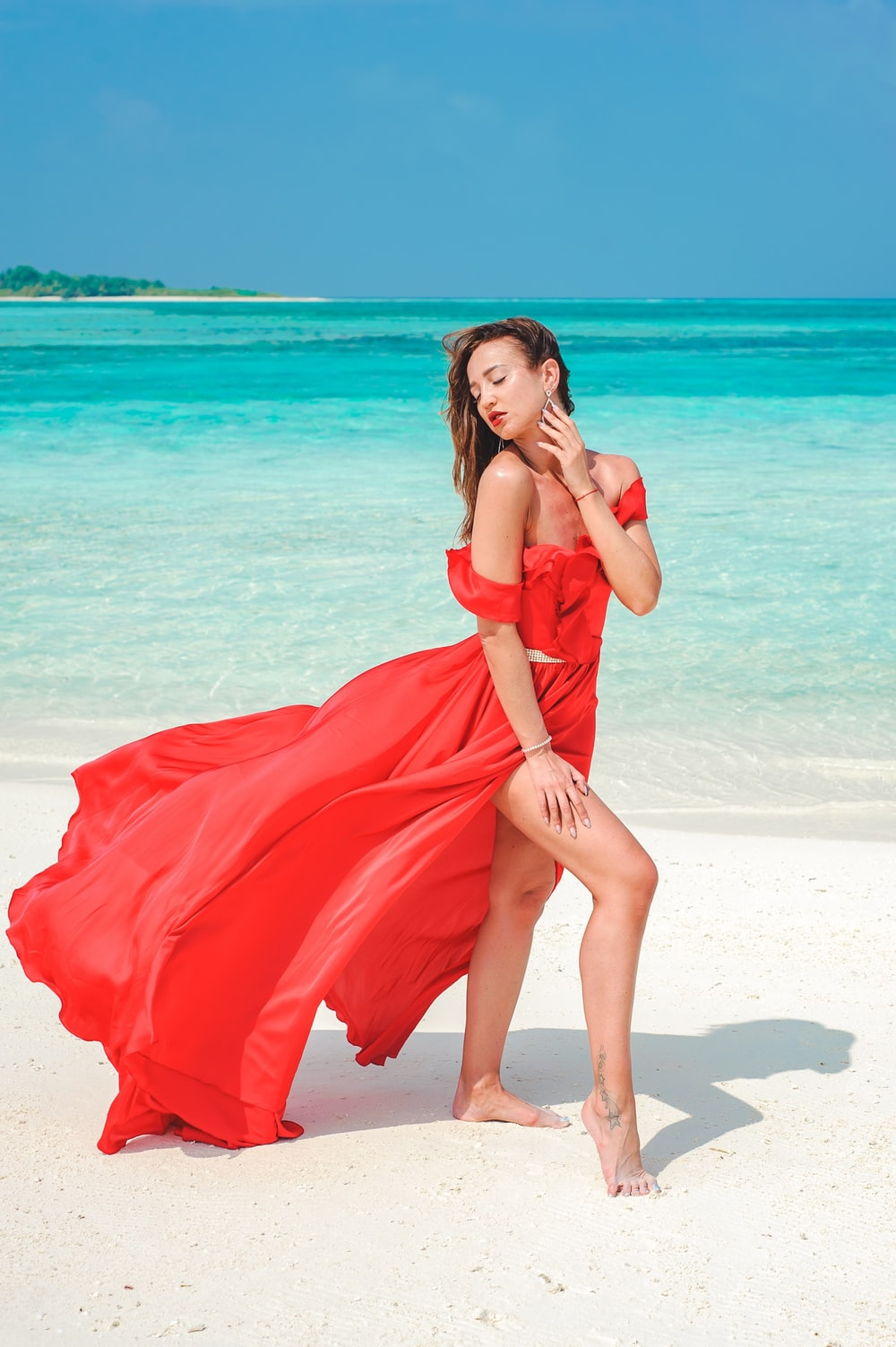 woman in red tube dress standing on beach during daytime