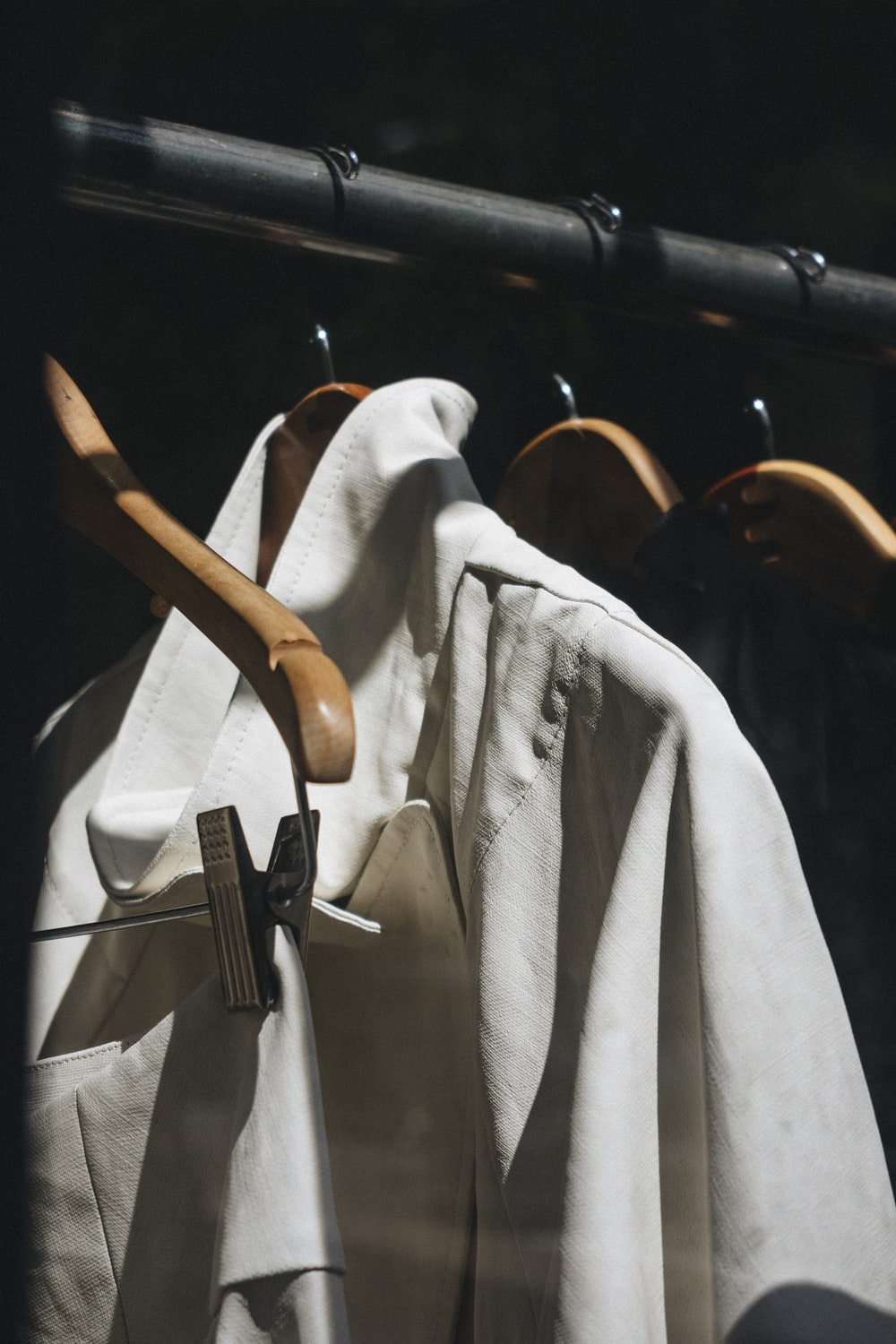 white dress shirt hanged on brown wooden clothes hanger