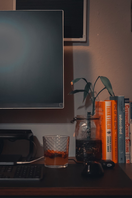 clear drinking glass beside silver flat screen tv