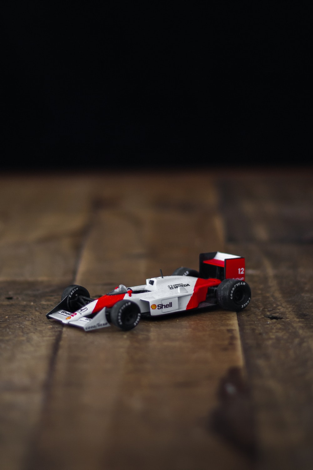 red and white lego car on brown wooden table