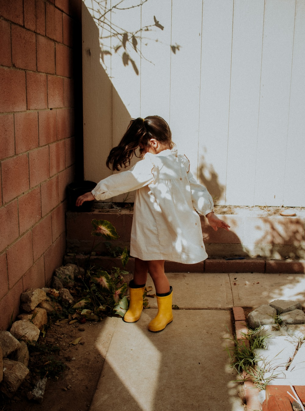 girl in white coat and yellow boots standing beside brown brick wall
