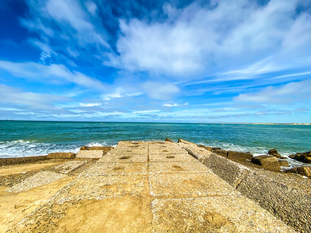 brown concrete pathway near sea under blue sky during daytime