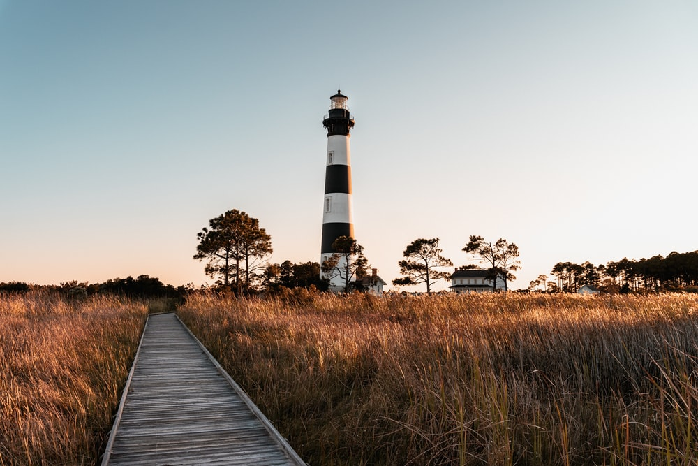 white and black lighthouse near green grass field during daytime