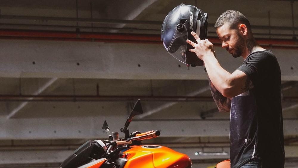 man in orange helmet riding orange motorcycle