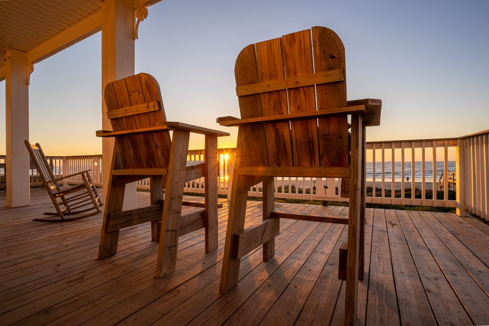 two brown wooden armchairs on brown wooden deck during daytime