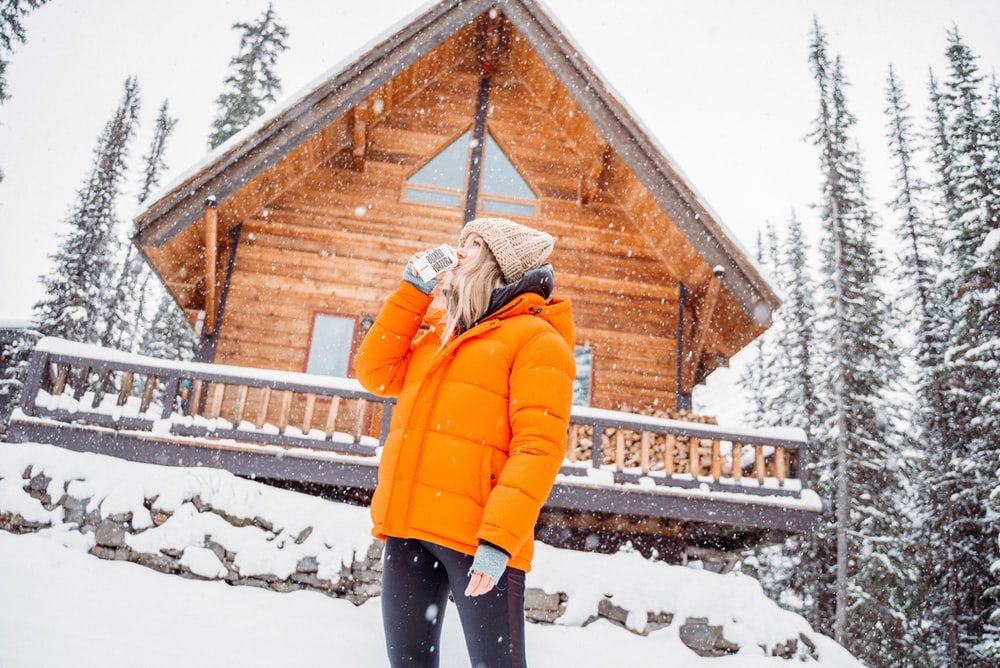 person in orange jacket standing on snow covered ground