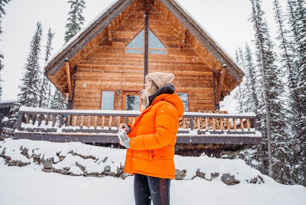 woman in orange jacket standing on snow covered ground