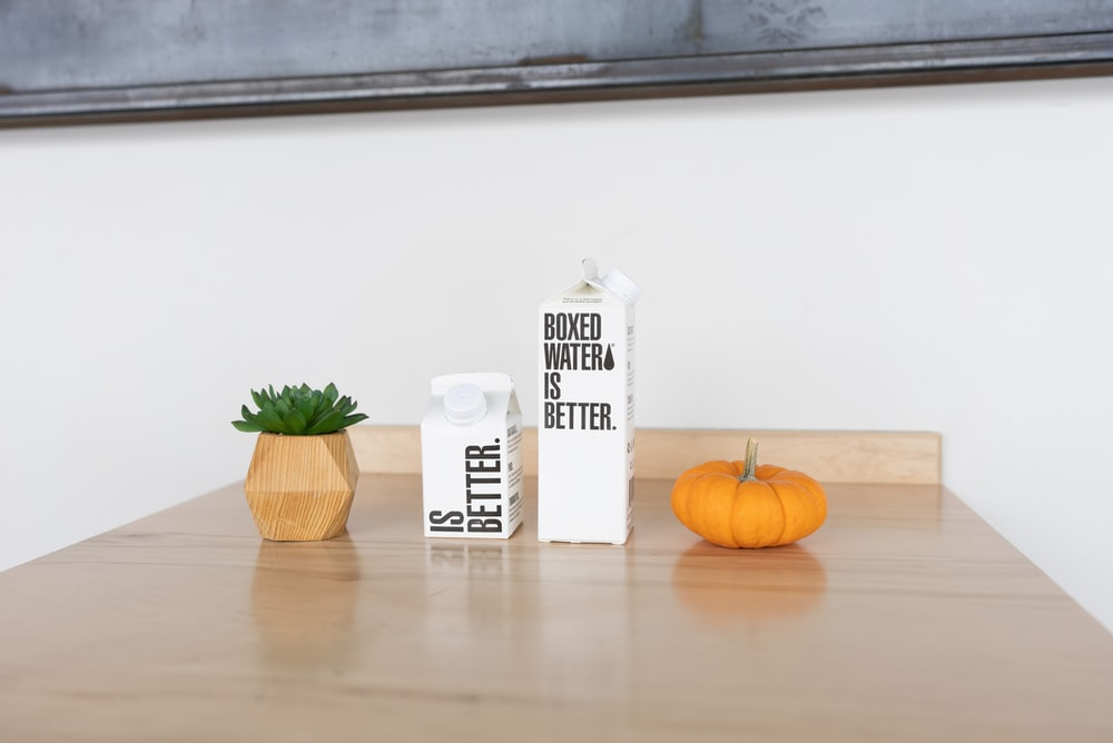 white and black labeled carton beside orange pumpkin on brown wooden table