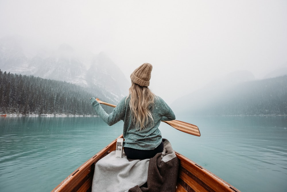 woman in gray long sleeve shirt sitting on brown wooden boat on body of water during