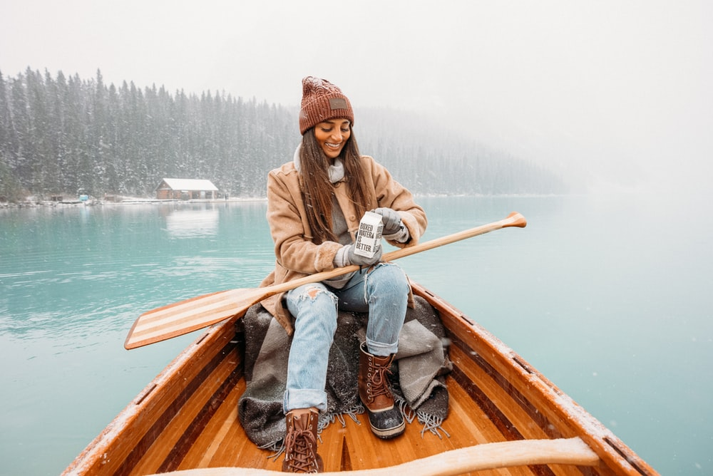 man in brown jacket and blue denim jeans sitting on brown wooden boat during daytime