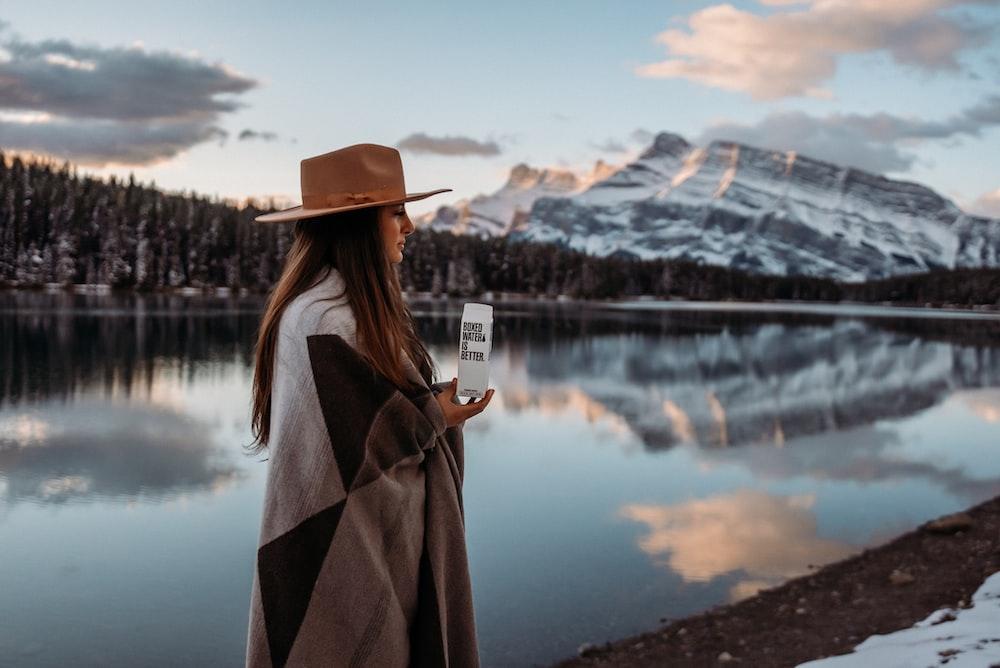 woman in brown coat wearing brown hat standing near lake during daytime