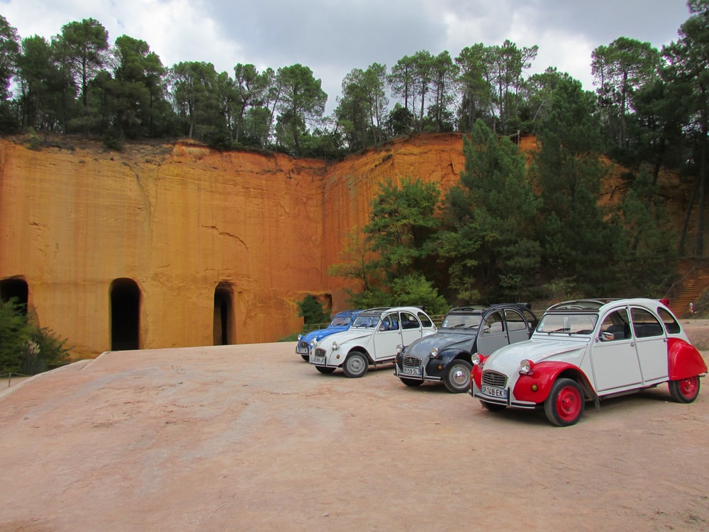 white and red cars parked beside brown concrete wall