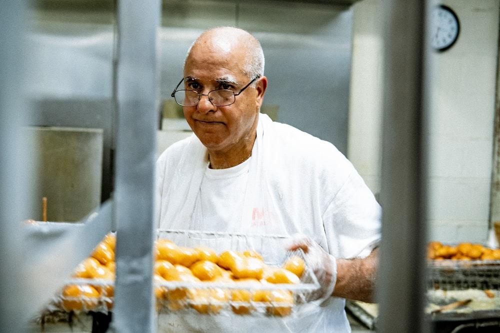 man in white crew neck t-shirt holding tray of orange fruits