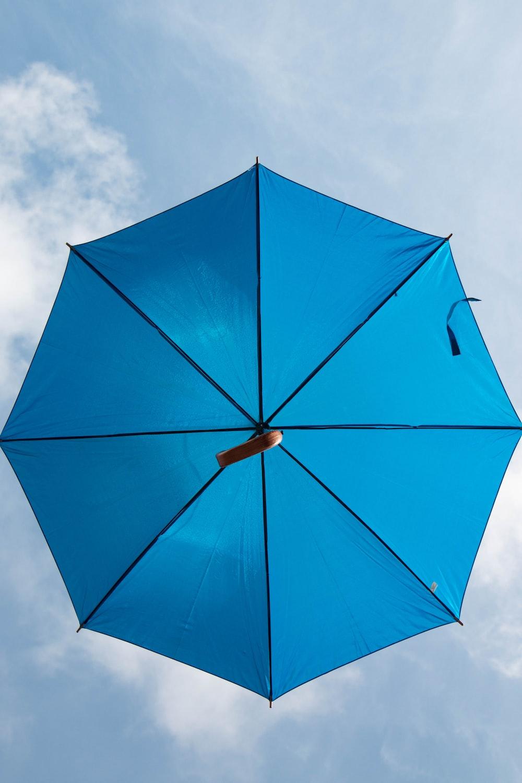blue umbrella under white sky