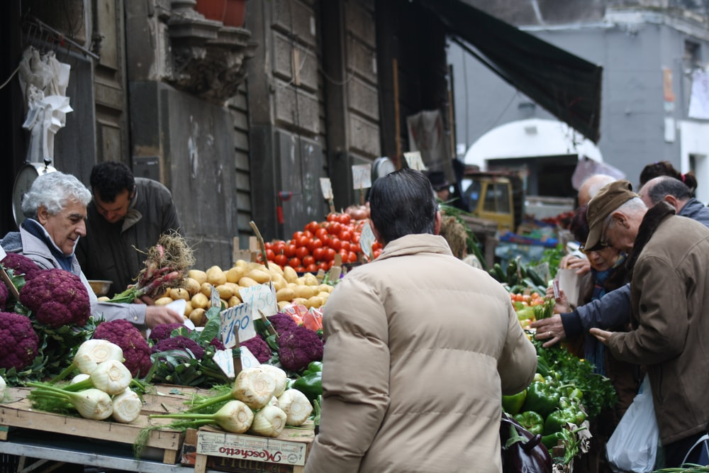 man in brown coat standing in front of fruit stand