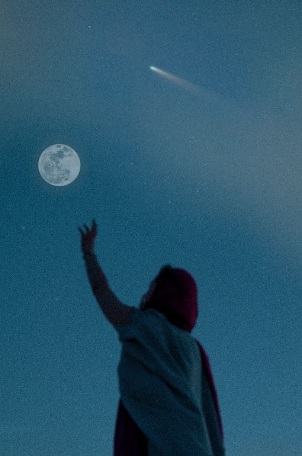 person in red hoodie looking at moon