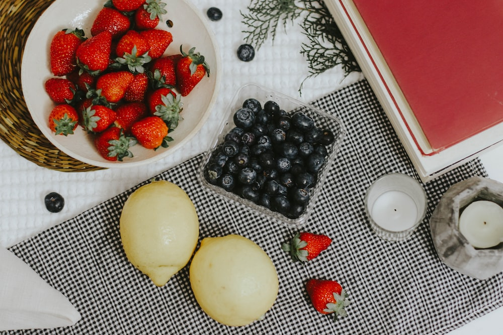 sliced strawberries and blue berries on white ceramic plate