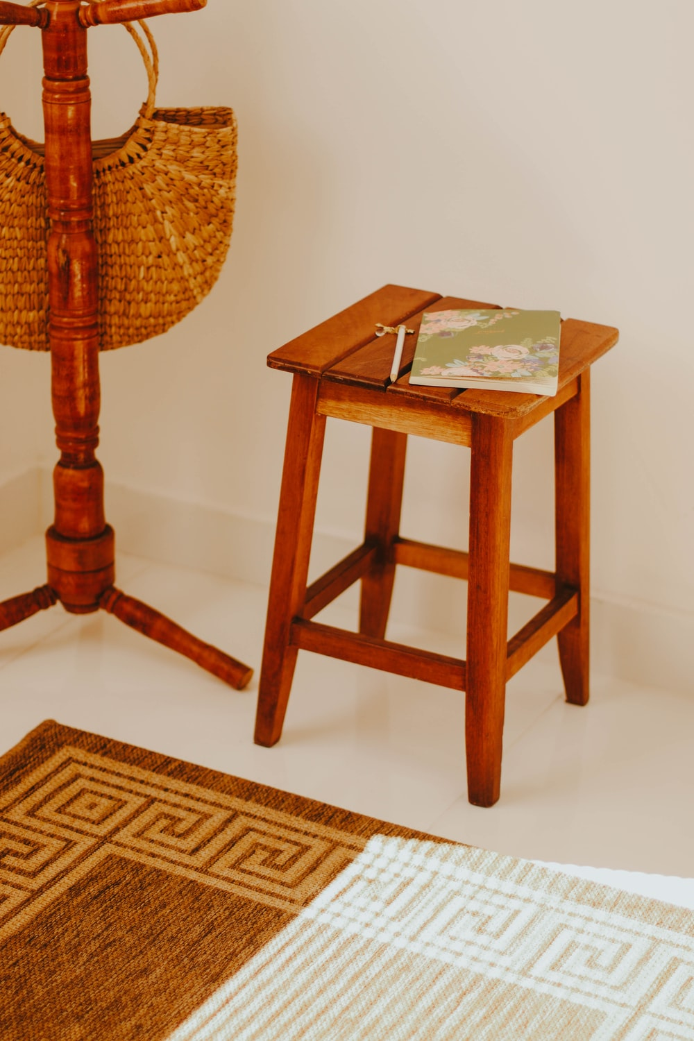 brown wooden table with white and green book on top