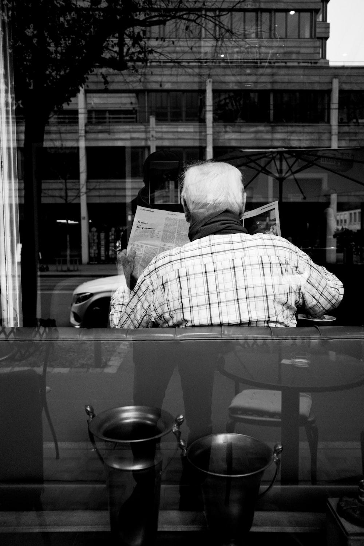 man in plaid shirt reading newspaper