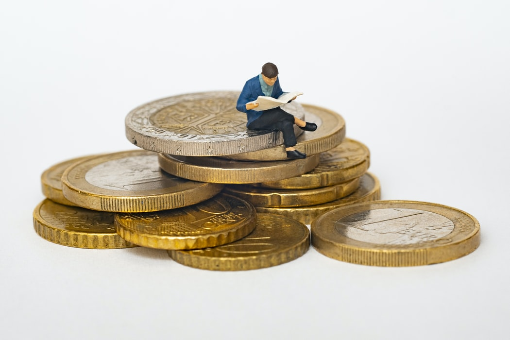 Figure of man sitting on pile of gold euro coins while reading a newspaper