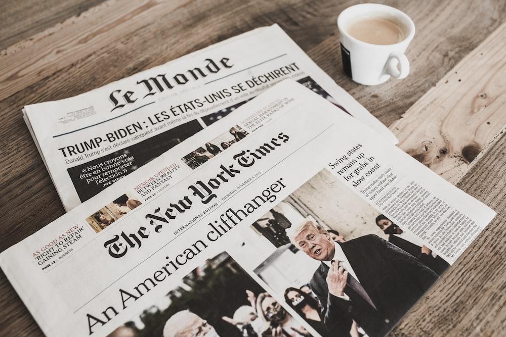 white newspaper beside white ceramic mug on brown wooden table