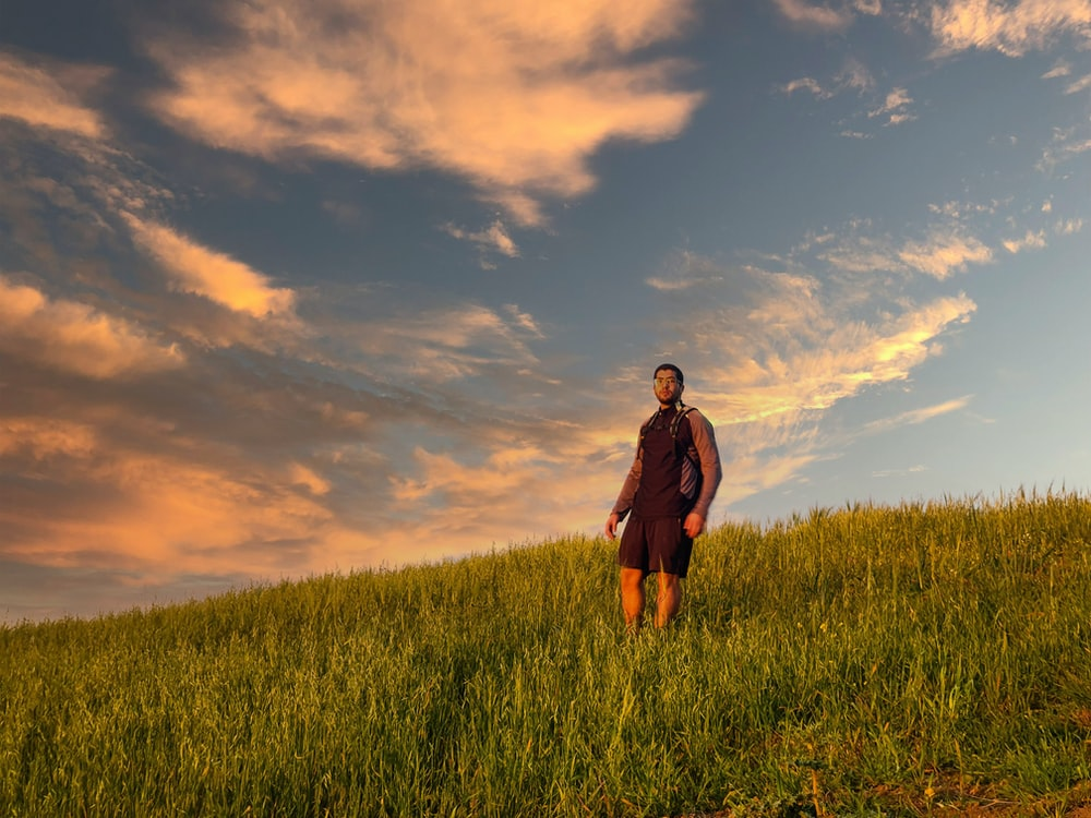 woman in black jacket standing on green grass field under cloudy sky during daytime