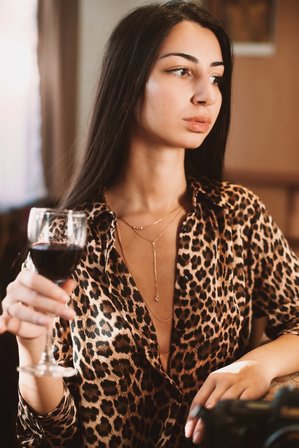 woman in brown and black leopard print long sleeve shirt holding clear wine glass