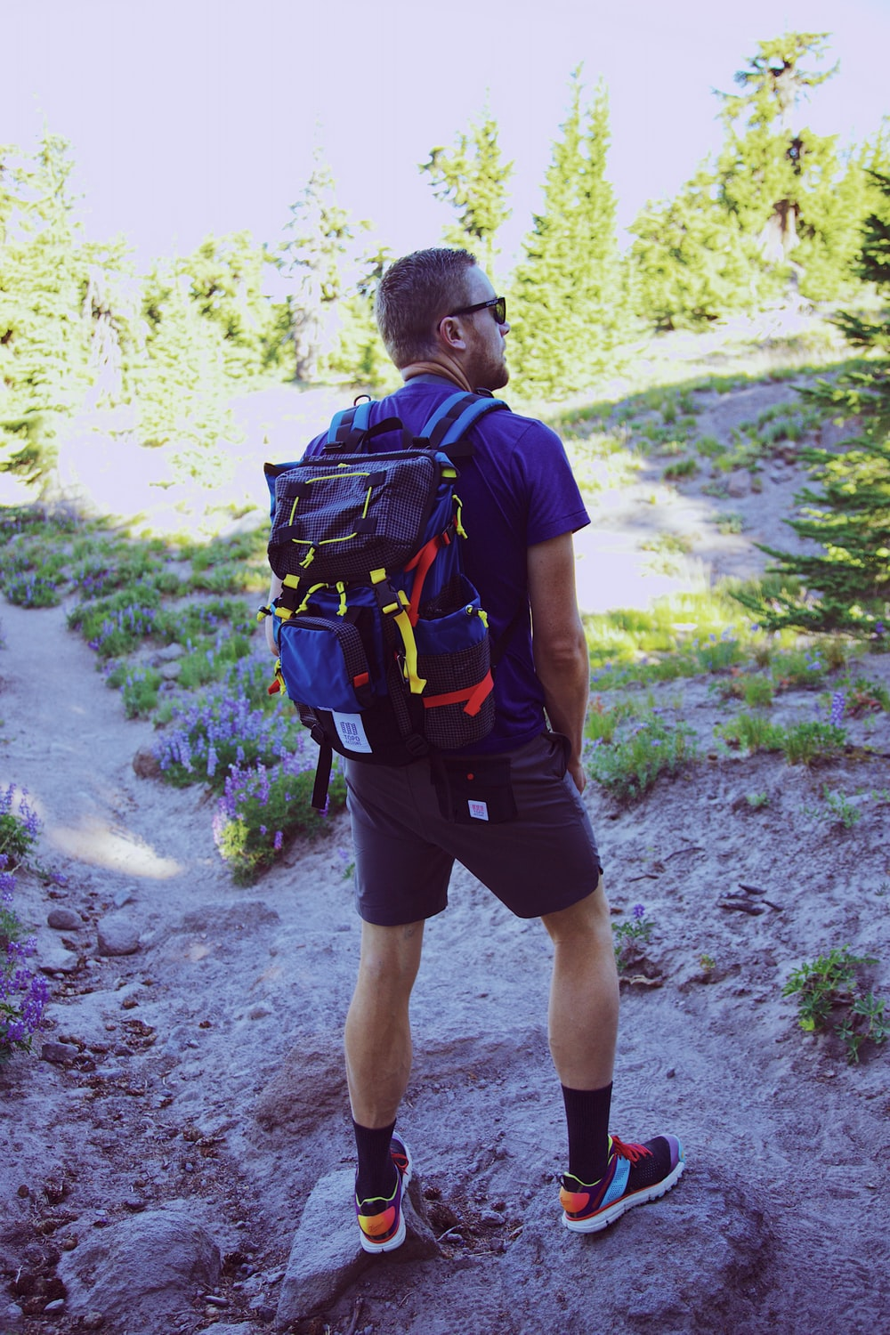 man in blue t-shirt and black shorts carrying black and blue hiking backpack walking on during