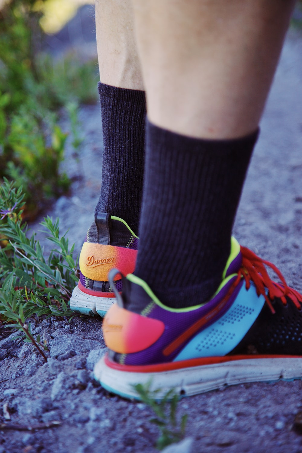 person wearing black and blue nike socks and orange and blue nike sneakers